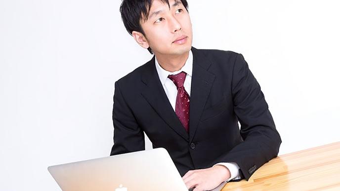 パソコンと手書きで悩む男性