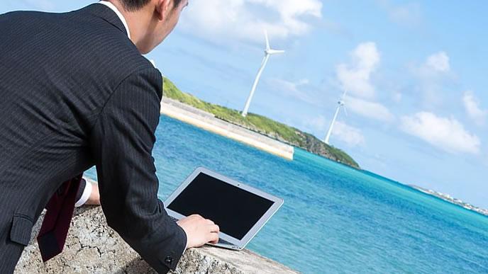 海岸でパソコンを使う非常識な男性