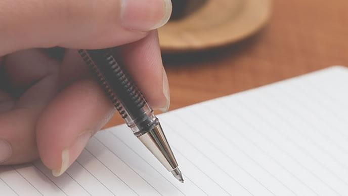 ボールペンでメモを取ろうとする手