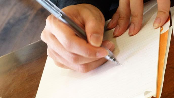 ボールえペンで書類をかく手