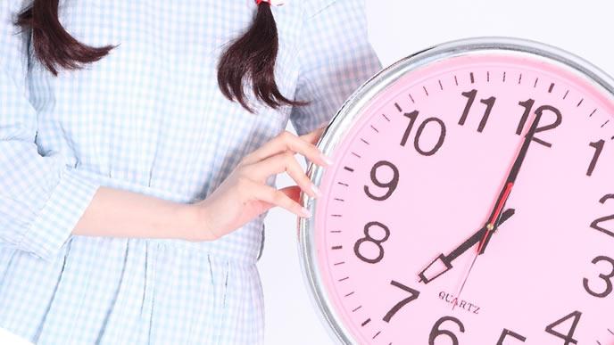 大きい時計を持った女性