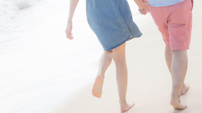 幸せそうに浜辺を歩くカップル