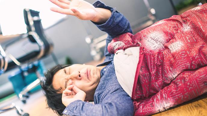 会社に寝泊りする睡眠不足の男性