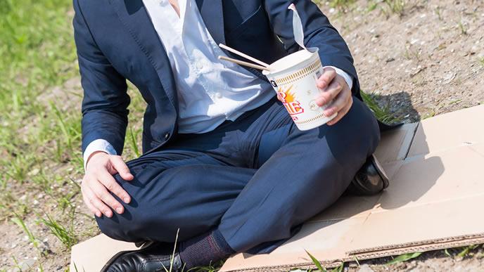 家がなく野原でラーメンを食べる男性