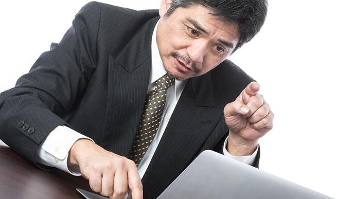 人差し指でパソコンを駆使する男性