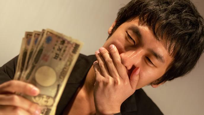 お金を手にして微笑んでいる男性