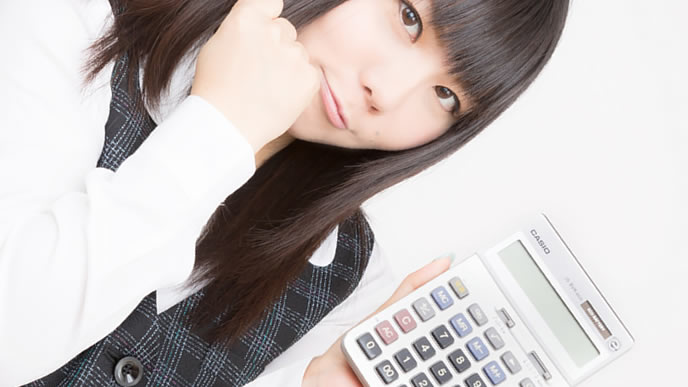 電卓で給料の計算をする女性