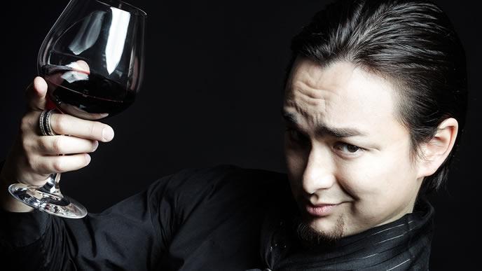 ワイン片手にニヤっとする男性