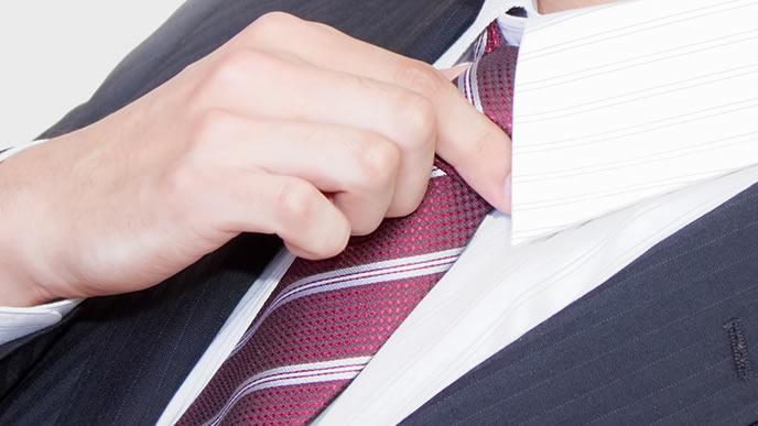 ストライプ柄のネクタイを締める男性