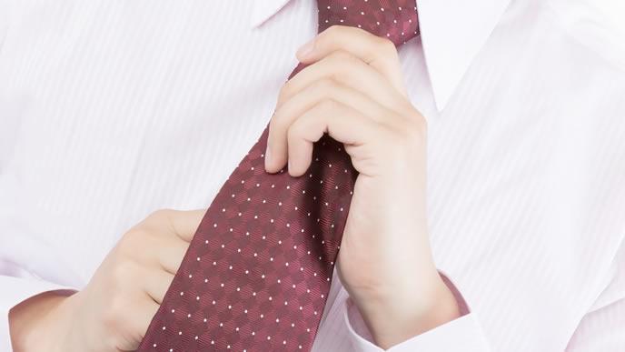 オシャレなドット柄のネクタイを締める男性
