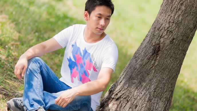 木陰で休憩するTシャツ男性