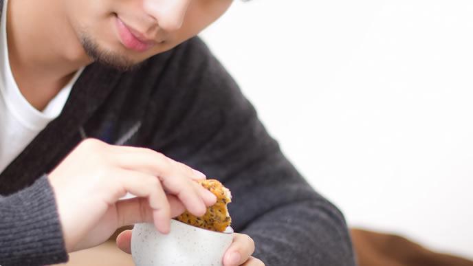 一人でせんべいをお茶に漬せられるようになった男性