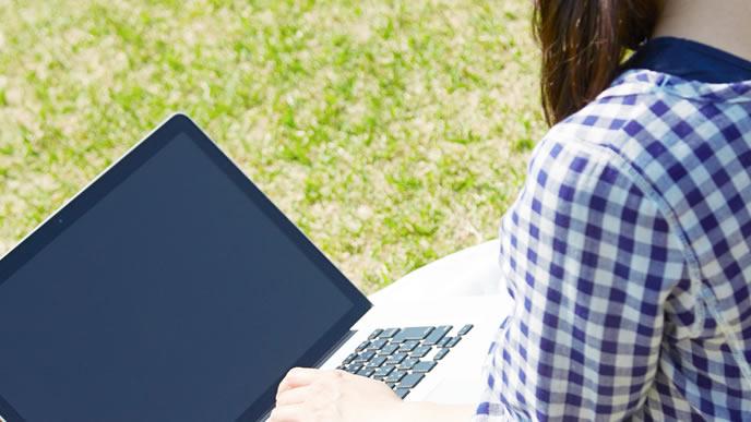 外の公園で転職活動中の女性