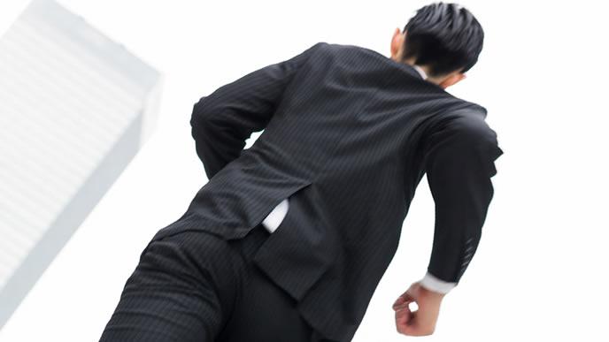 スーツでビルの隙間を走る男性