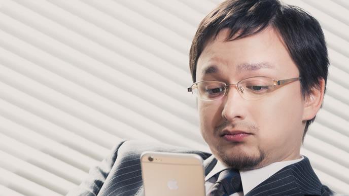 憂鬱な気分で携帯電話を眺めている男性