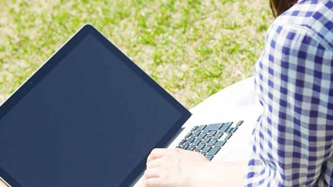 公園で内定辞退のメールを送る女性