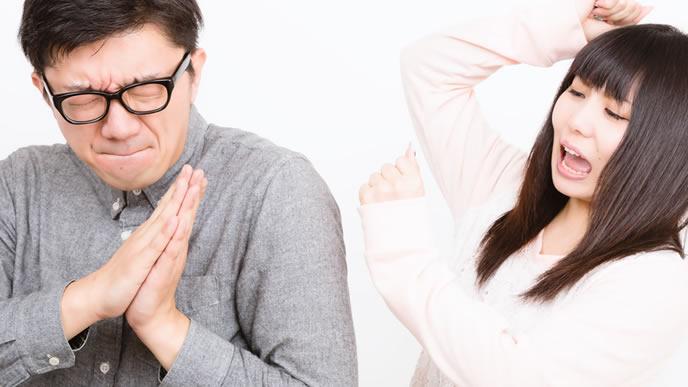 必死に謝る喧嘩中のカップル
