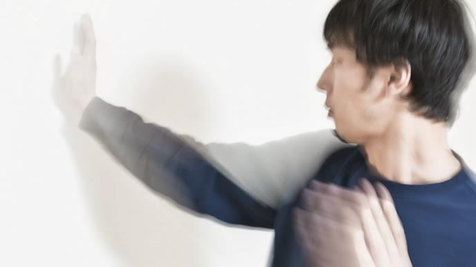 壁に張り手をし続ける男性
