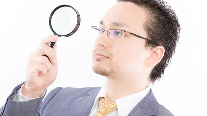 虫眼鏡で今後のビジョンを見る男性