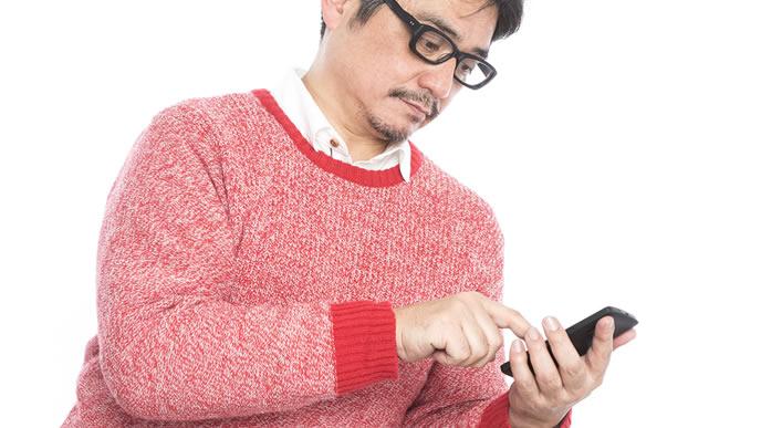 転職サイトをスマホで見ている中年男性