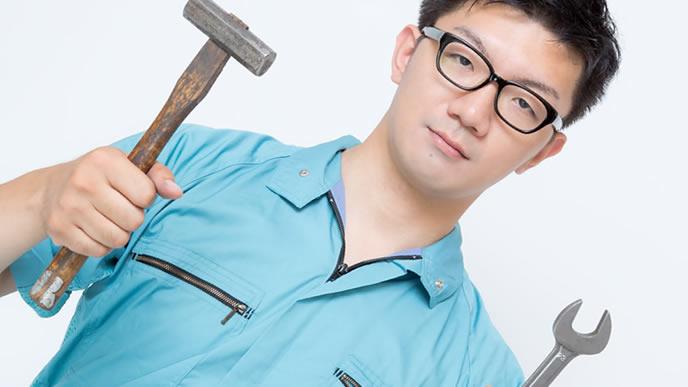 工場の器具を持ってポーズを取る男性
