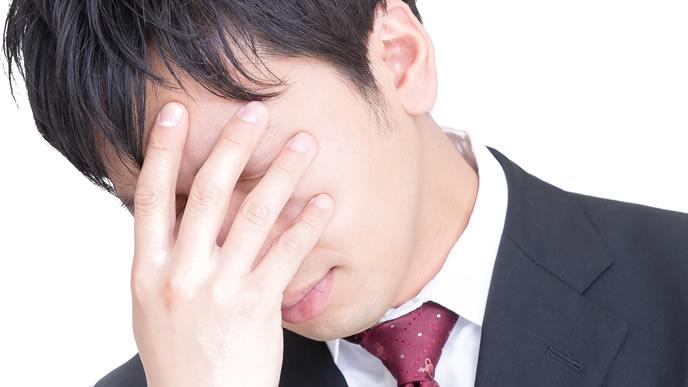仕事のミスで落ち込む男性