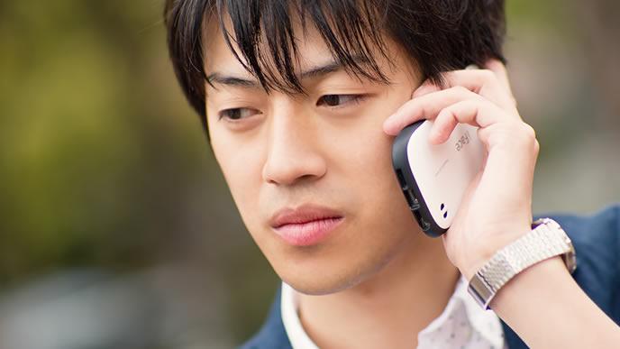 忙しい時間帯を外して電話連絡をする男性