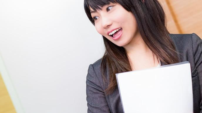 書類をクリアファイルに入れて持ち運ぶ女性