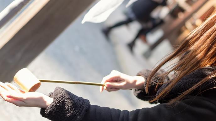 神社でお清めをする女性