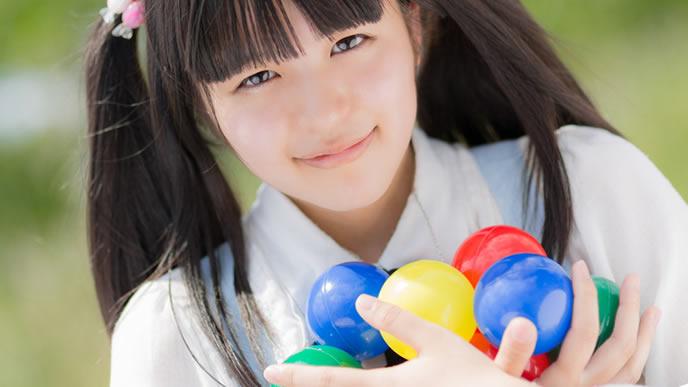 いっぱいのカラーボールと夢を持っている少女