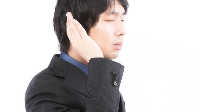 耳を澄まして話を聞く男性