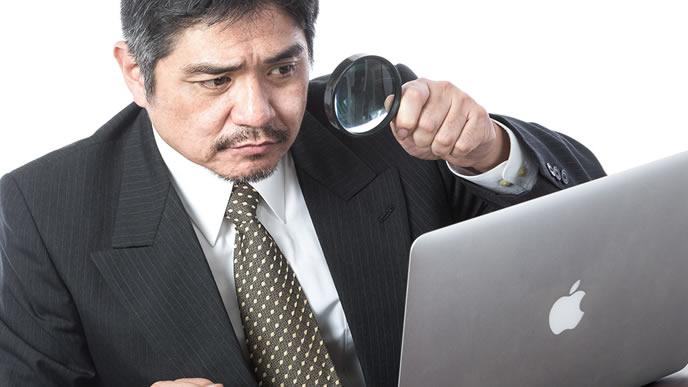 虫眼鏡とパソコンを使って企業研究する男性