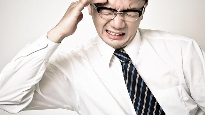 仕事のミスが怖くて考え込む男性