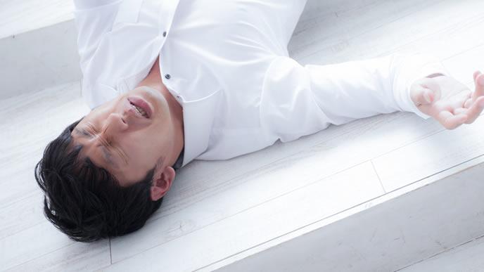 体調不良で床にころがる男性