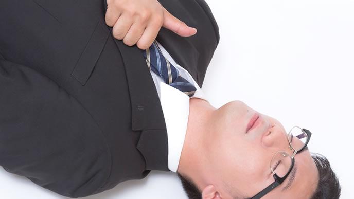 仕事に疲れて倒れながらもアピールする男性