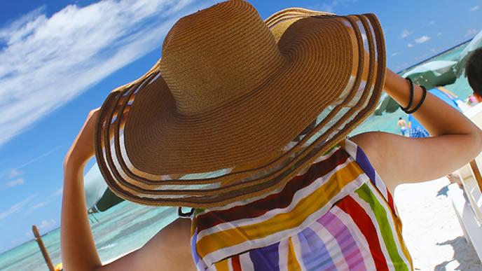 まぶしい日差しで帽子をかぶる女性