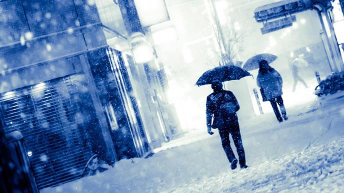 雪の中を歩くビジネスマン