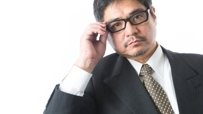 メガネを直して説教する学校教諭の男性