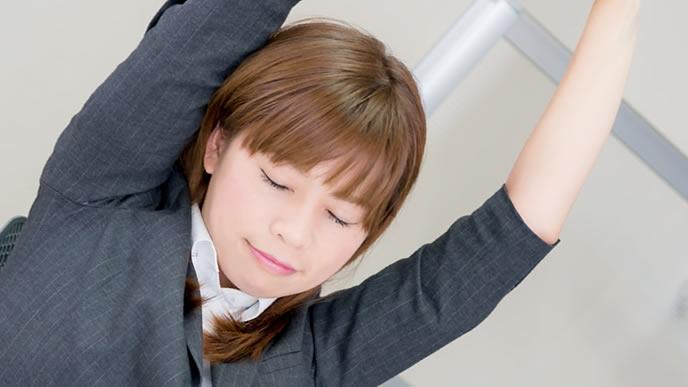 伸びをして疲れを和らげる女性