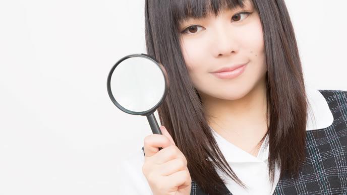 虫眼鏡で新しい情報を発見した女性