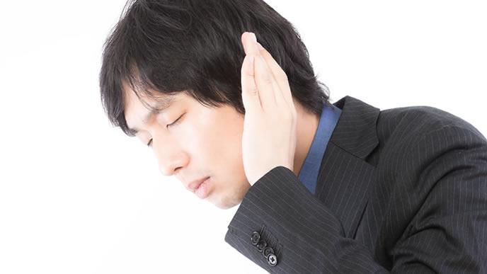 耳を澄まして聞き入る男性