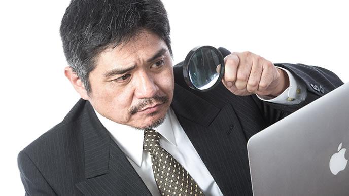 老眼が始まりパソコンの画面を虫眼鏡で確認する上司