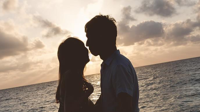 夕焼けをバックに結婚を誓い合うカップル