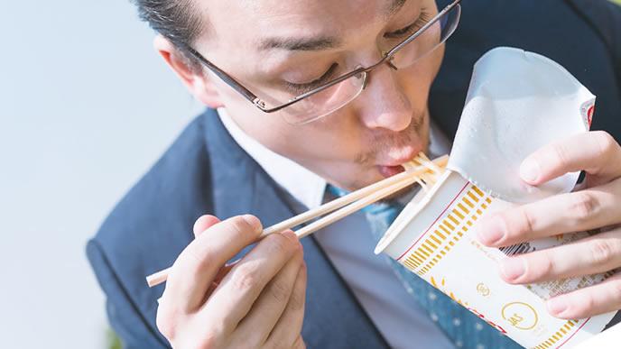 カップラーメンを食べて食費を節約する男性