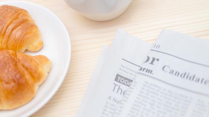 英字の新聞と朝食のクロワッサン