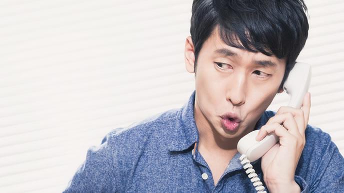 電話で辞退の連絡を入れる男性