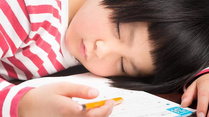 疲れ果て眠りにつく小学生