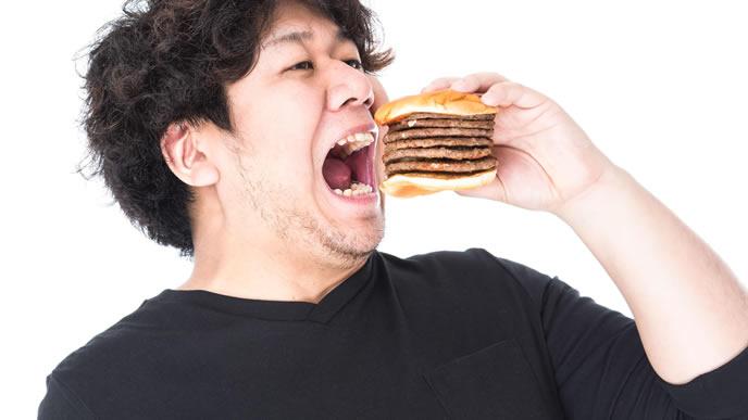 肉が多いハンバーガーを食べる男性