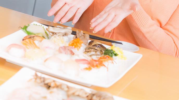 珍しい外食でお寿司を食べる女性