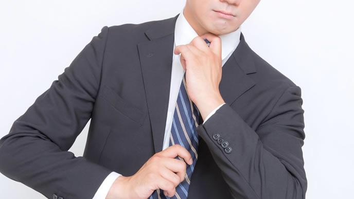 大きな商談に向けてネクタイを締め直すビジネスマン